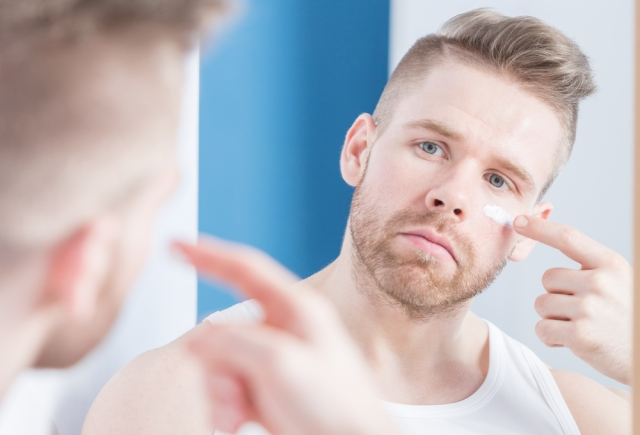 Man applying moisturizer on his face.