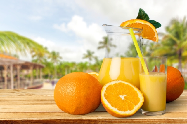 Closeup of orange juice and oranges on a wooden table.